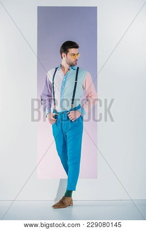 Handsome Stylish Young Man In Suspenders And Eyeglasses Looking Away While Standing In Opening On Gr