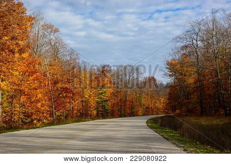 Fall road in Pictured Rocks National Lakeshore, Munising, MI, USA. Gorgeous display of fall colors, leaves, red, orange, green and yellow trees with both side of empty road leading your eye through the picture. poster