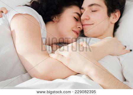 Couple In Love Sleeps Cuddling In Bed