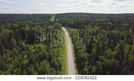Aerial View Of White Car Driving On Country Road In Forest. Aerial View Flying Over Old Patched Two