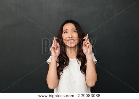 Portrait of praying young woman wearing casual clothing begging god please looking up with keeping fingers crossed isolated over dark gray background