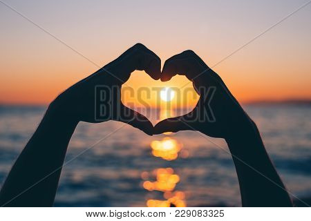 Male Hands In The Shape Of A Heart At Sunset