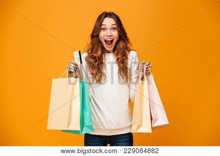 Image of excited screaming young woman standing isolated over yellow background looking camera holding shopping bags and credit card.