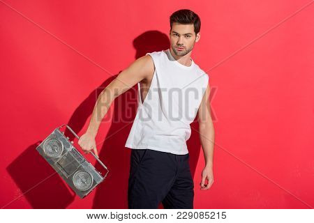 Handsome Young Man Holding Tape Recorder And Looking At Camera On Pink