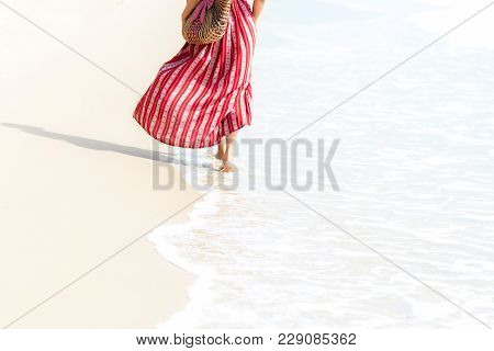 Summer Vacations. Smiling Woman Wearing Fashion Summer Walking On The Sandy Ocean Beach. Happy Woman