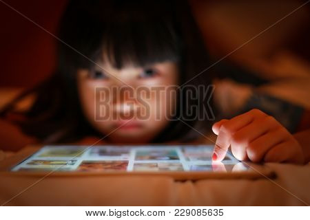 Selective Focus On Finger Tip Hand Of Child Using Online Tablet While Lying On The Bed, In Dim Light