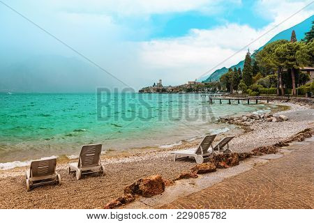 Beach Lounger At Lake Shore Gardasee With Wavy Water, Tourist Destination Malcesine Italy