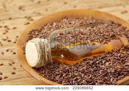 Top View Closeup Picture Flax Seeds And Linseed Oil In A Glass Bottle On A Wooden Background, Shallo