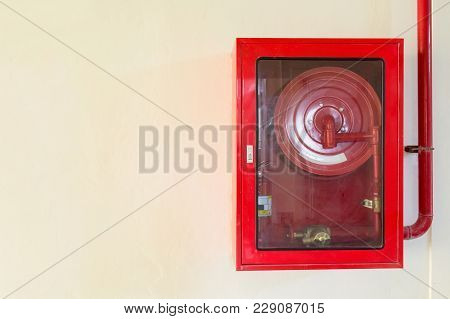 Fire Extinguisher And Fire Hose Reel On Concrete Wall. Copy Space