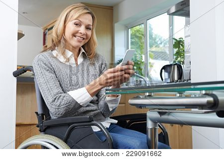 Portrait Of Disabled Woman In Wheelchair Using Mobile Phone At Home