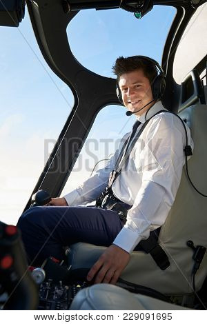 Portrait Of Pilot In Cockpit Of Helicopter During Flight