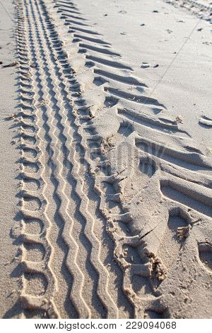 Tyre Tracks In Sand. Tractor Tire Tread Imprint On Beach. Geometric Zigzag Pattern Left By Industria