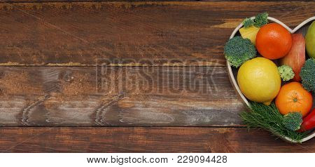 Fruits And Vegetables In Heart Shaped Wooden Box. Broccoli, Apples, Pepper, Tangerine Over Wooden Ba