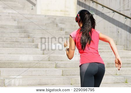 Young, fit and sporty woman running up the stairs. Fitness, sport, urban jogging and healthy lifestyle concept.