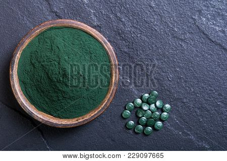 Green Spirulina Powder In Bowl And Pills . Nature Medicine