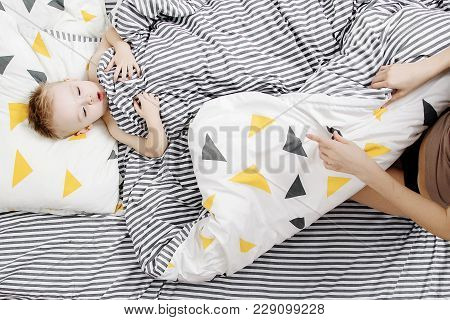 Little Boy In Bed. The Boy Wakes Up In The Morning. The Child Is Under The Blanket