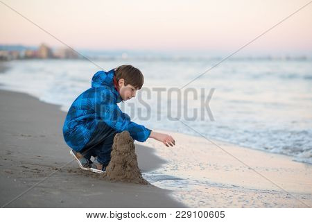 Young boy builds sand castle at the winter beach. Cute 11 years old boy at seaside, evening time. Kid's outdoor portrait.