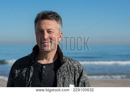 Handsome middle-aged man at the beach. Attractive happy smiling mid adult male model posing at seaside. Outdoor portrait of beautiful man.