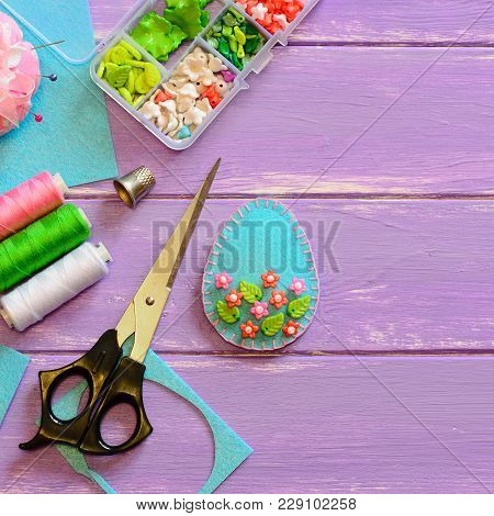 Blue Felt Easter Egg, Scissors, Thread Set, Box With Plastic Beads, Thimble, Felt Scrap On The Purpl