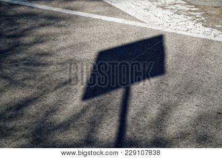 Shadow Street Sign On Asphalt Road, Urban Background.