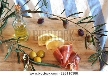 Still Life With Spanish A Pata Negra Ham, Olives And Olive Oil In A Bottle On A Wooden Cutting Board