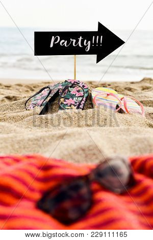 a pair of sunglasses on a beach towel in the foreground, and two pairs of flip-flops and an arrow-shaped signboard with the text party written in it in the background, on the sand of a quiet beach