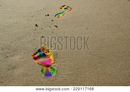 Footprints In Rainbow Colors On The Beach