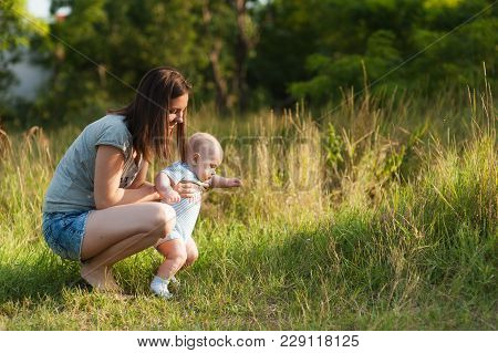 First Steps. Young Beautiful Woman In Green Grass Background Learning Cute Child Baby Boy To Walk On