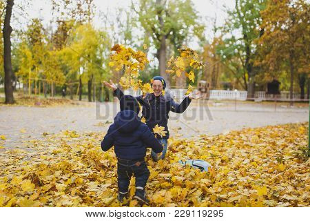 Young Woman Walk In Fall Park With Little Cute Child Baby Boy, Toss Throw Up Dry Yellow Autumn Leave