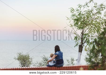 Young Woman Sitting On Bench, Looking At Sea Scarlet Sunset, Hugging Little Cute Child Boy On Nature