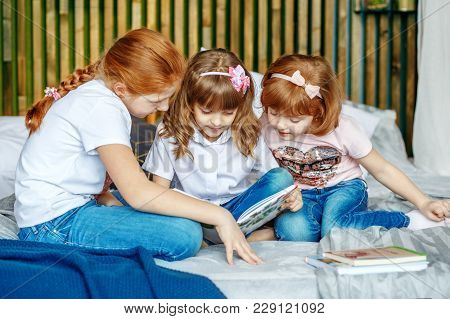 Little Girls Are Considering A Book. The Concept Of Lifestyle, Childhood, Education, Family, School.