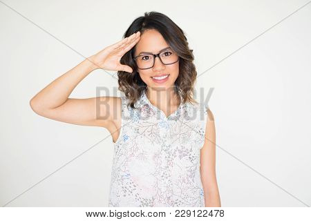 Closeup Portrait Of Smiling Young Beautiful Dark-haired Woman Looking At Camera And Saluting. Allegi