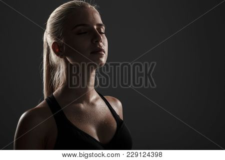 Portrait of a sweaty fitness woman dressed in sportswear with eyes closed over dark background