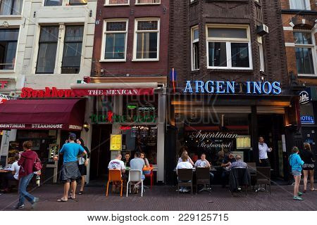 Amsterdam, The Netherlands - June 10, 2014: Beautiful Sreets Of Amsterdam With Outdoors Cafe On Summ