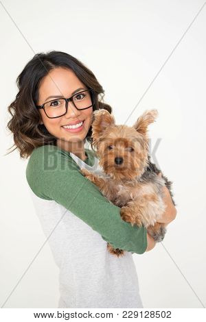 Closeup Portrait Of Smiling Young Attractive Woman Looking At Camera And Holding Yorkshire Terrier.