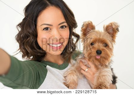 Closeup Portrait Of Smiling Young Attractive Woman Holding Yorkshire Terrier And Taking Selfie Photo