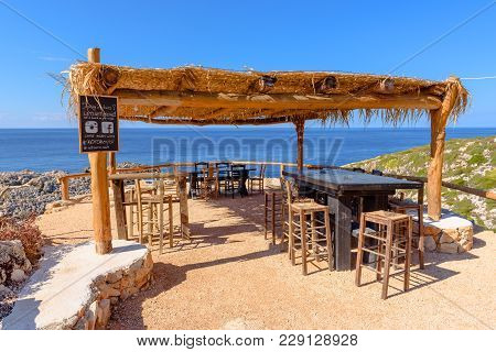 Zakynthos, Greece - October 1, 2017: Greek Tavern With Tables And Chairs On Cliff With View Of Blue