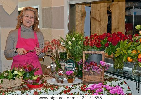 Florist woman on the work on flowers background.