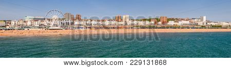 Brighton Beachfront panoramic view with the Ferris Wheel promenade and shingle beach pictured from the Brighton Palace Pier on a sunny summer day in June 2013