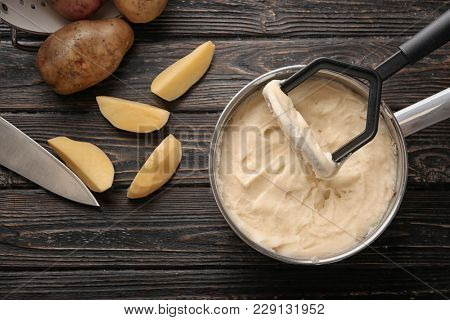 Kitchen utensil and mashed potatoes in cookware on wooden table