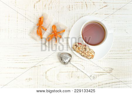 Top View On Cup Of Tea And Few Bar Of Muesli. White Wooden Background