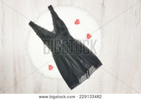 Fashion Concept. Black Lacy Nightie On White Fur. Red Heartshaped Candles