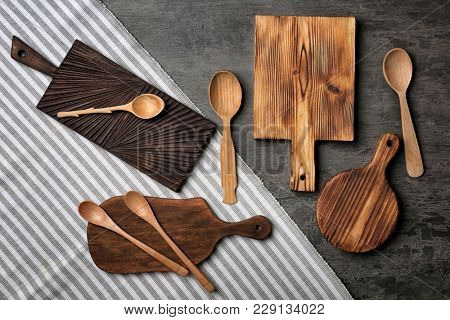 Wooden kitchen utensils on grey background