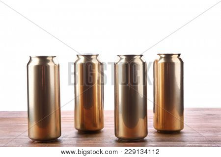 Cans of beer on wooden table against white background