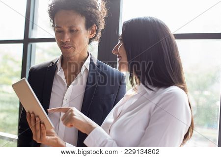 Multi-ethnic Business Executives Discussing Financial Analysis. Smiling Young Business Lady Showing
