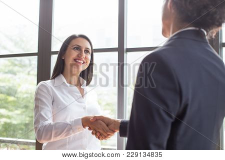 Cheerful Confident Female Manager Concluding Deal And Shaking Partners Hand After Negotiation. Happy