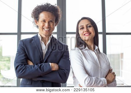 Happy Confident Multiethnic Entrepreneurs Looking At Camera And Standing In Office. Cheerful Success