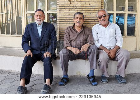 Kashan, Iran - April 27, 2017: Three Elderly Iranian Men Sit On The Concrete Seat With Their Backs T