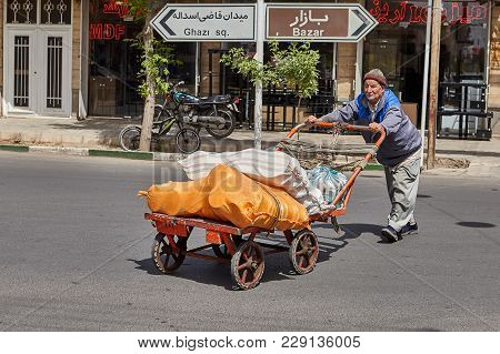 Kashan, Iran - April 27, 2017: An Elderly Man Pushes A Handcart In Front Of Him On The Roadway Of A