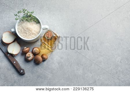 Ingredients for risotto with mushrooms on light background